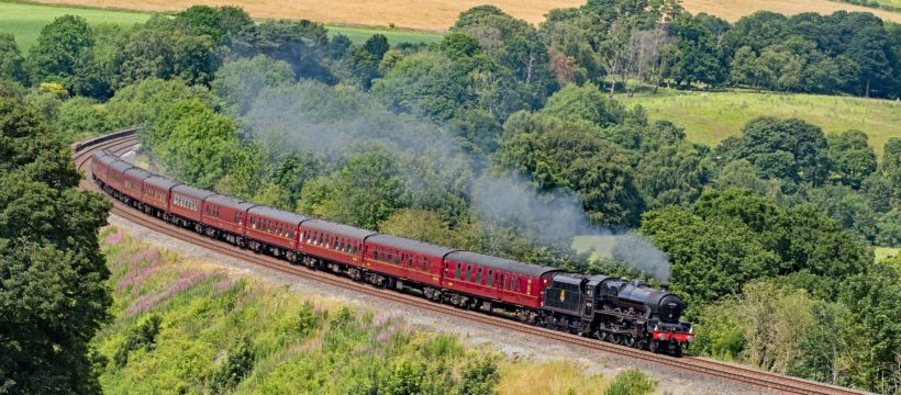 "Cumbria has seen a typical British summer with cloud and occasional rain. On 13 July 2019 in a rare patch of good light, former LMS Stanier ""Jubilee"" 45690 ""Leander"", looking every inch the late 1950s and reunited with her original tender, powers around Armathwaite curve on the Settle – Carlisle line as she heads south with train 1Z87, the 14.12 Carlisle – Carnforth leg of the Euston bound ""Cumbrian Mountain Express""."